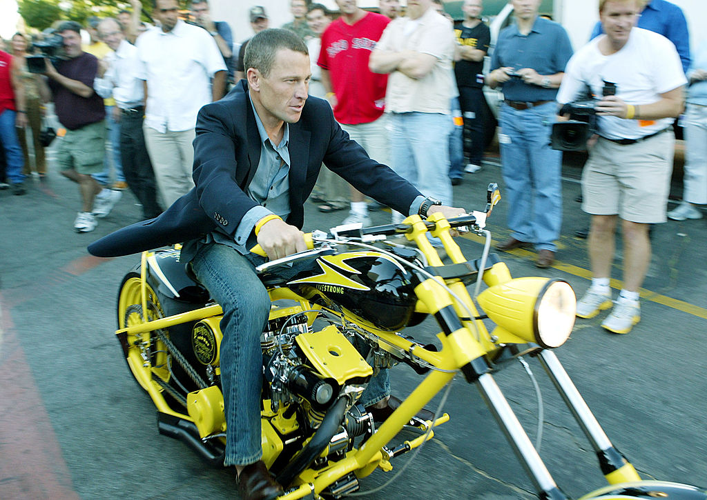 Lance Armstrong on a motorcycle smiling, slightly blurred