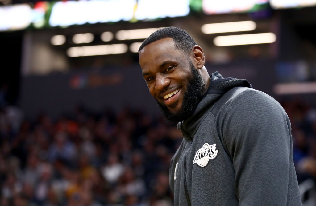 LeBron James smiling in a gray sweatshirt