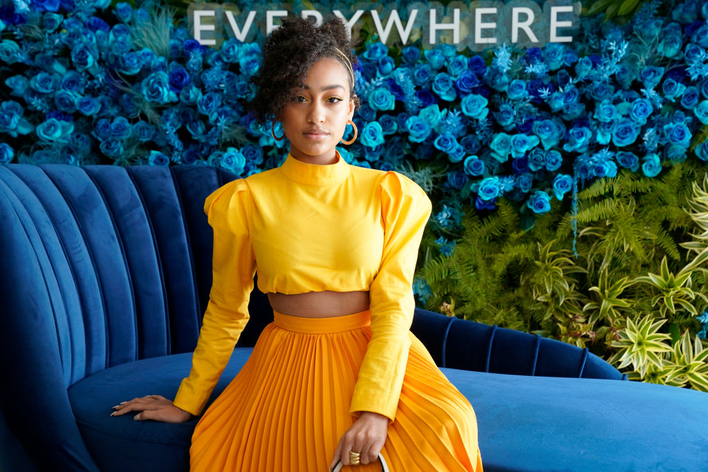 Lexi Underwood wearing a gold yellow outfit on a dark teal couch in front of a teal and green backdrop
