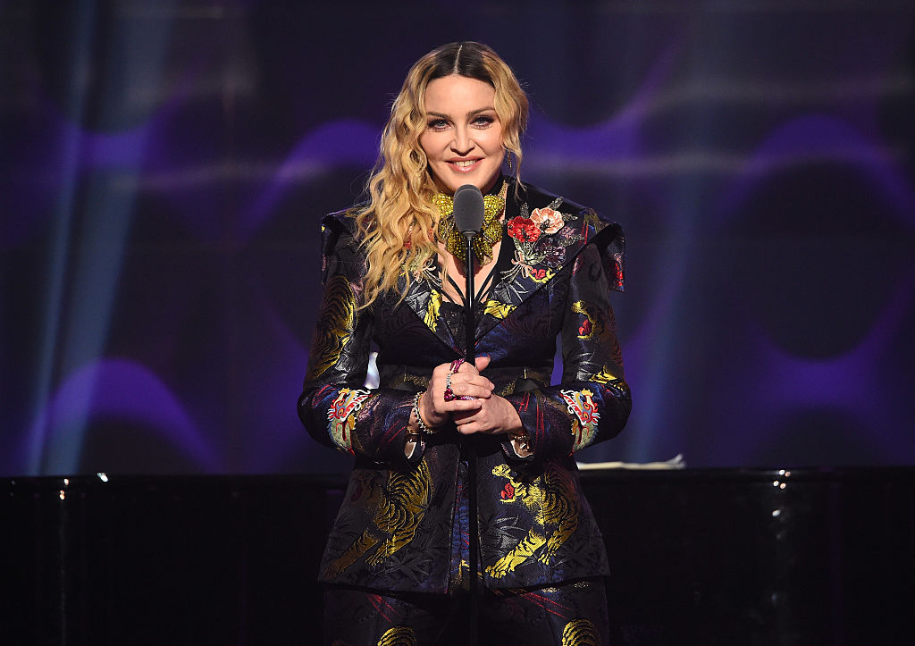 Madonna smiling on stage in front of a microphone