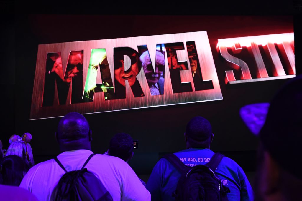 Marvel Studios logo lit up with people in backpacks looking up at the logo