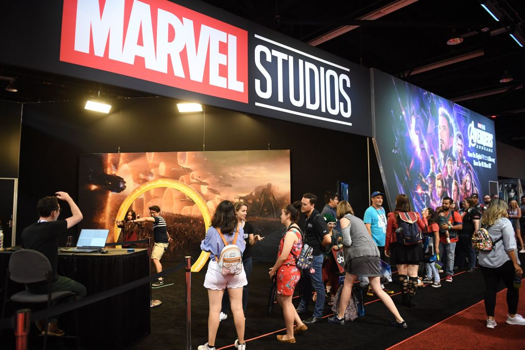 Marvel Studios banner over an entrance with groups of fans at a Disney fan event