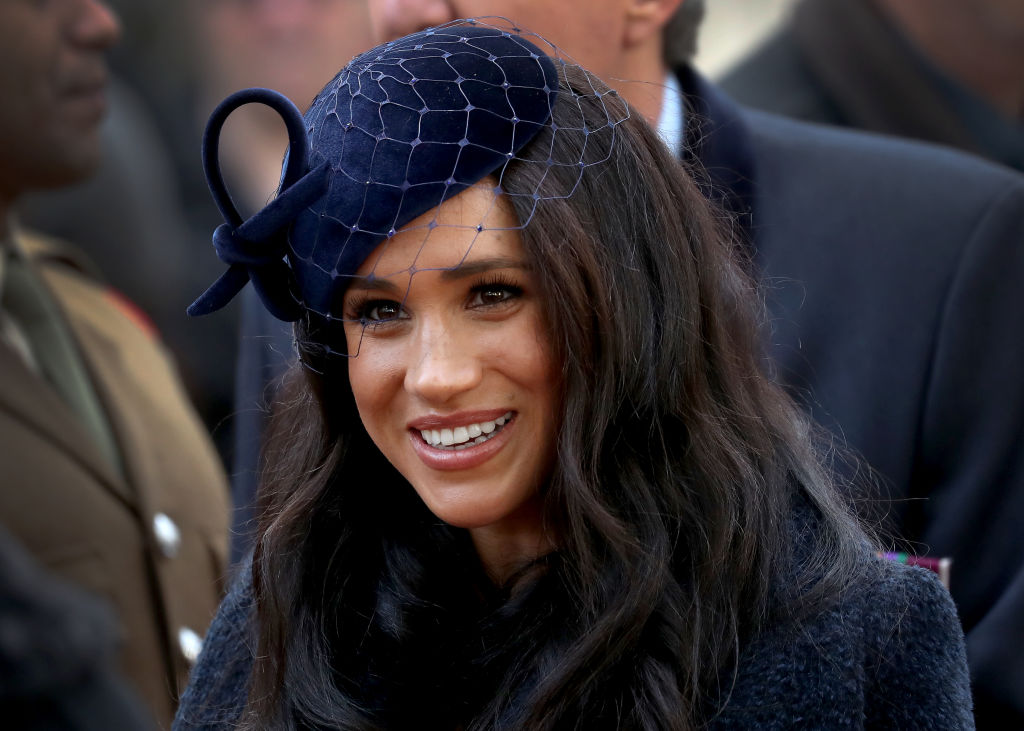 Meghan Markle smiling, looking away from the camera