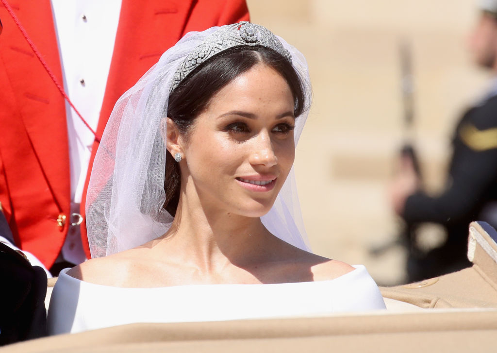 Meghan Markle smiling looking off camera wearing her wedding dress and veil