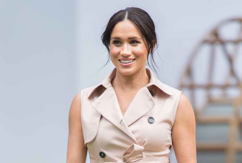Meghan Markle smiling looking off camera in a tan buttoned shirt