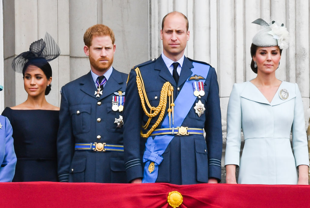 Meghan Markle, Prince Harry, Prince William, and Kate Middleton stand on the balcony of Buckingham Palace to view a flypast to mark the centenary of the Royal Air Force (RAF)