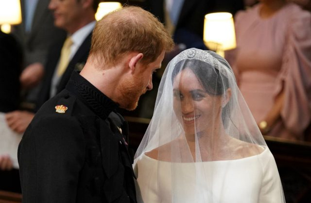Meghan Markle smiles at Prince Harry as they stand together during their royal wedding
