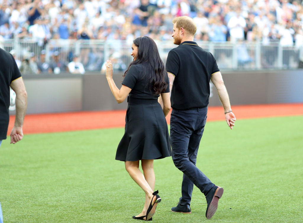 Prince Harry, Duke of Sussex and Meghan, Duchess of Sussex leave the field after accompanying Invictus Games competitors on the field for the ceremonial first pitch before game one of the London Series between the New York Yankees and the Boston Red Sox at London Stadium