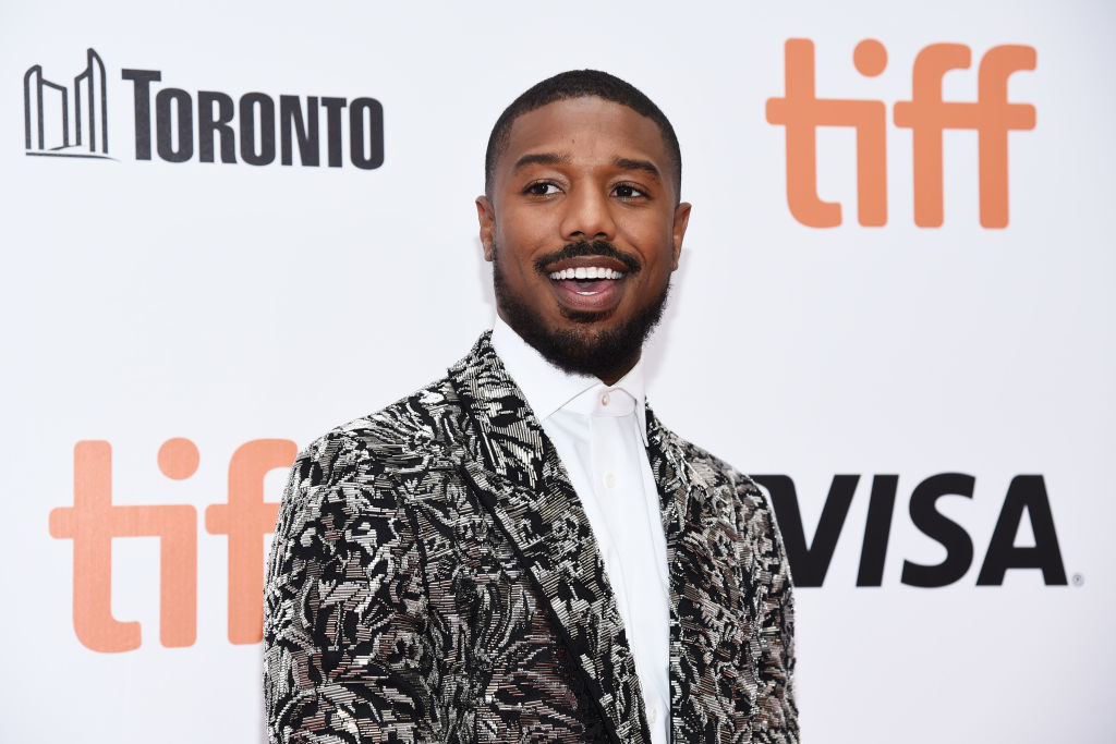 Michael B. Jordan smiling, looking away from the camera, in front of a white background with repeating logos