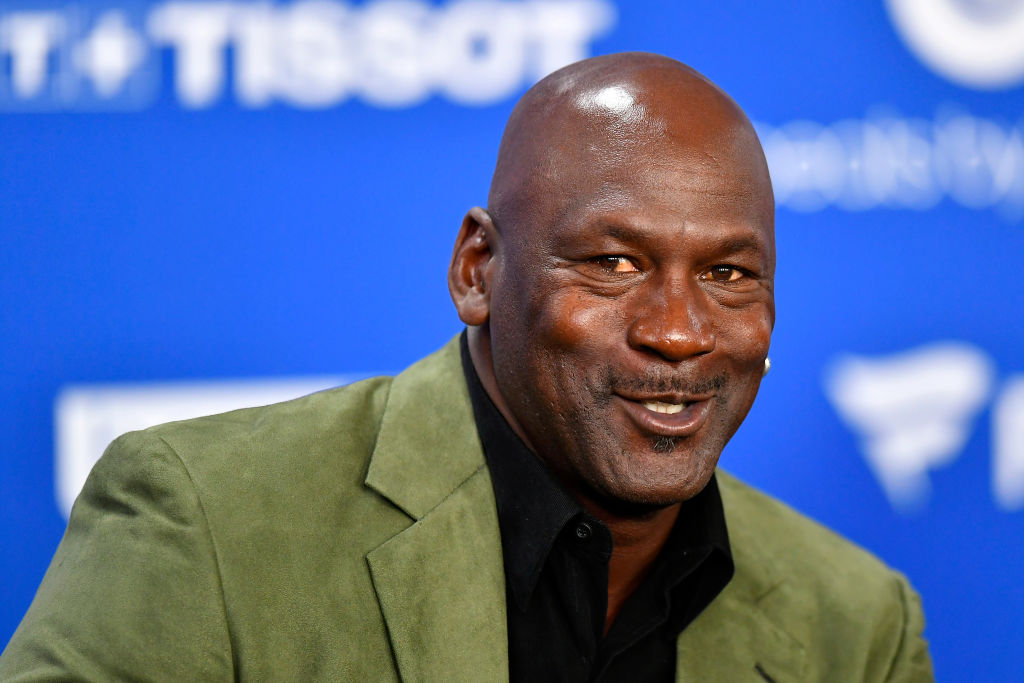 Michael Jordan smiling in front of a blue and white background