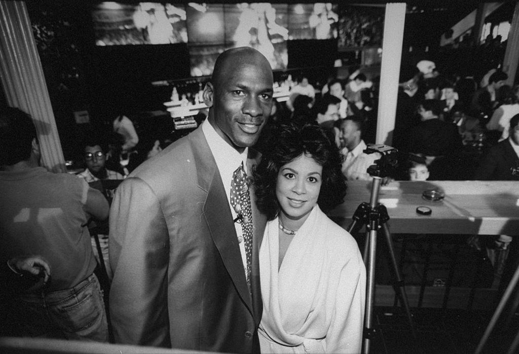 Chicago Bulls basketball star Michael Jordan posing w. wife Juanita at bar at the opening of his restaurant