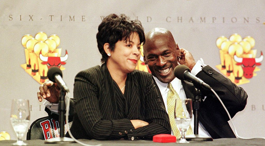 Michael Jordan of the Chicago Bulls (R) laughs as his wife Juanita is questioned by reporters about how her life will change with Michael Jordan's retirement, during a press conference 13 January at the United Center in Chicago, IL. Jordan is retiring from the NBA after 13 seasons. Jordan finished his career leading the Bulls to six NBA titles, five NBA Most Valuable Player awards, ten scoring titles and twelve NBA All-Star game appearances