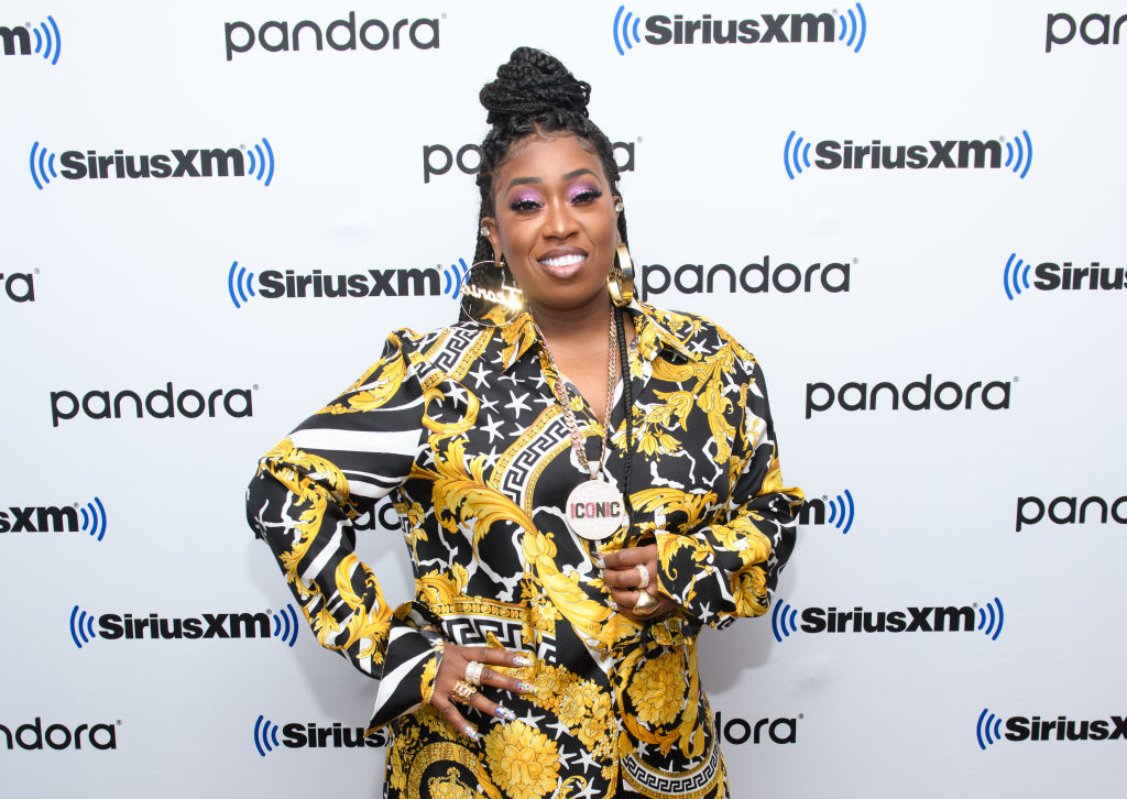 Missy Elliott smiling in front of a white and black repeating background