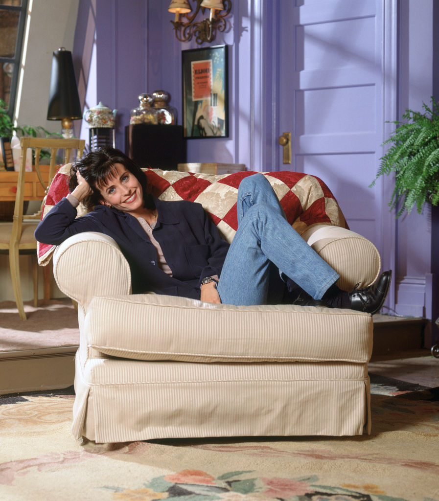 Courtney Cox as Monica Geller sitting in her apartment