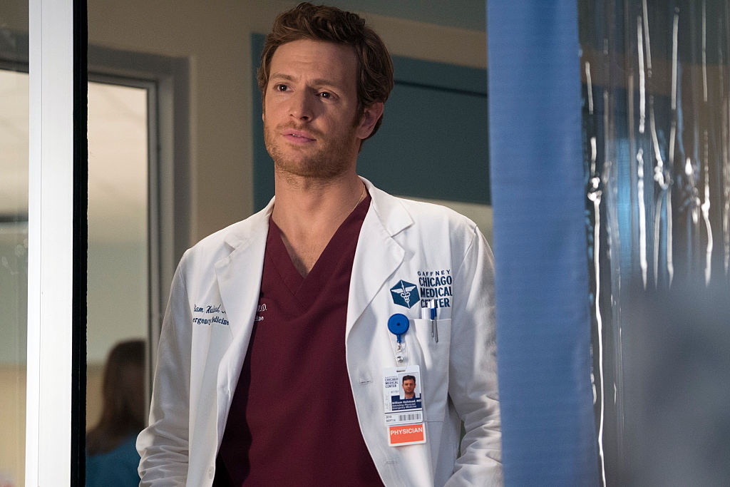 Nick Gehlfuss as Will Halstead in a doctor's coat and dark red scrubs