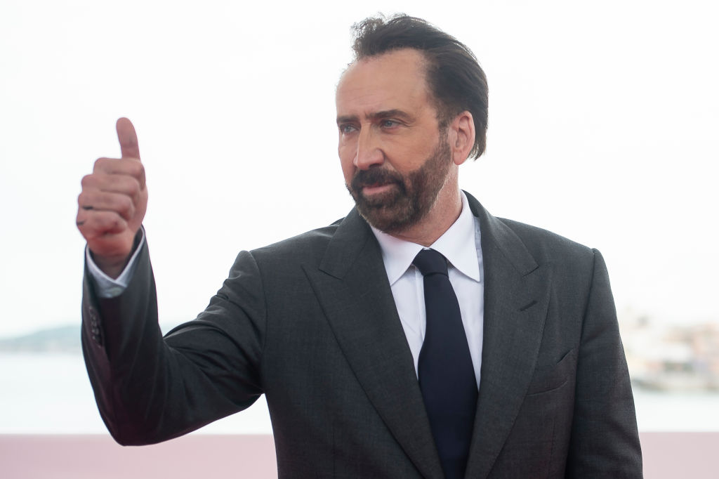 Nicolas Cage looking off camera and giving a thumbs up