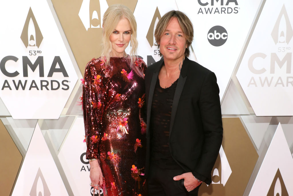 Nicole Kidman in a red sequin dress and Keith Urban in all black smiling in front of a textured background
