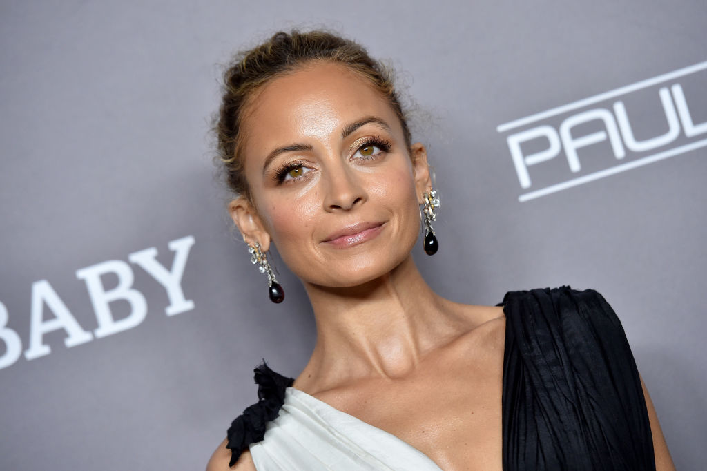 Nicole Richie smiling in front of a gray backdrop wearing black and white