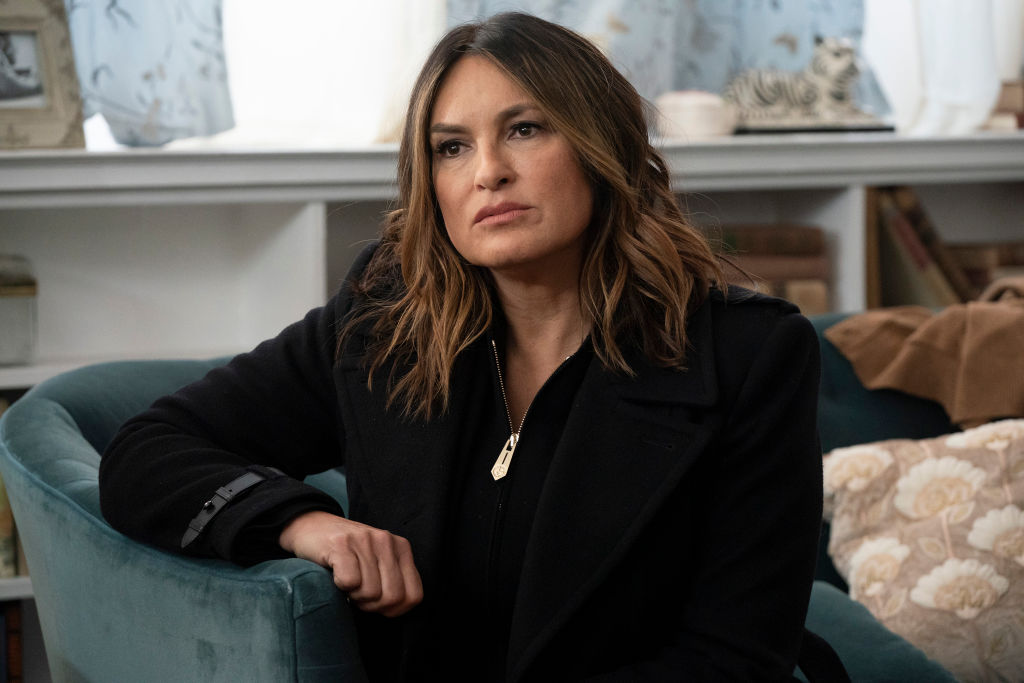 Mariska Hargitay as Captain Olivia Benson in all black sitting on a couch, looking away from the camera