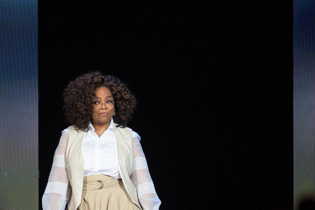 Oprah smiling while walking onto a stage