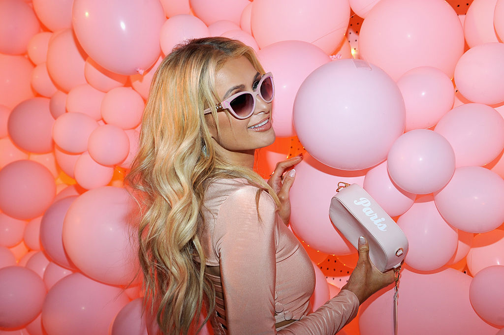 Paris Hilton smiling wearing sunglasses in front of a wall of pink balloons