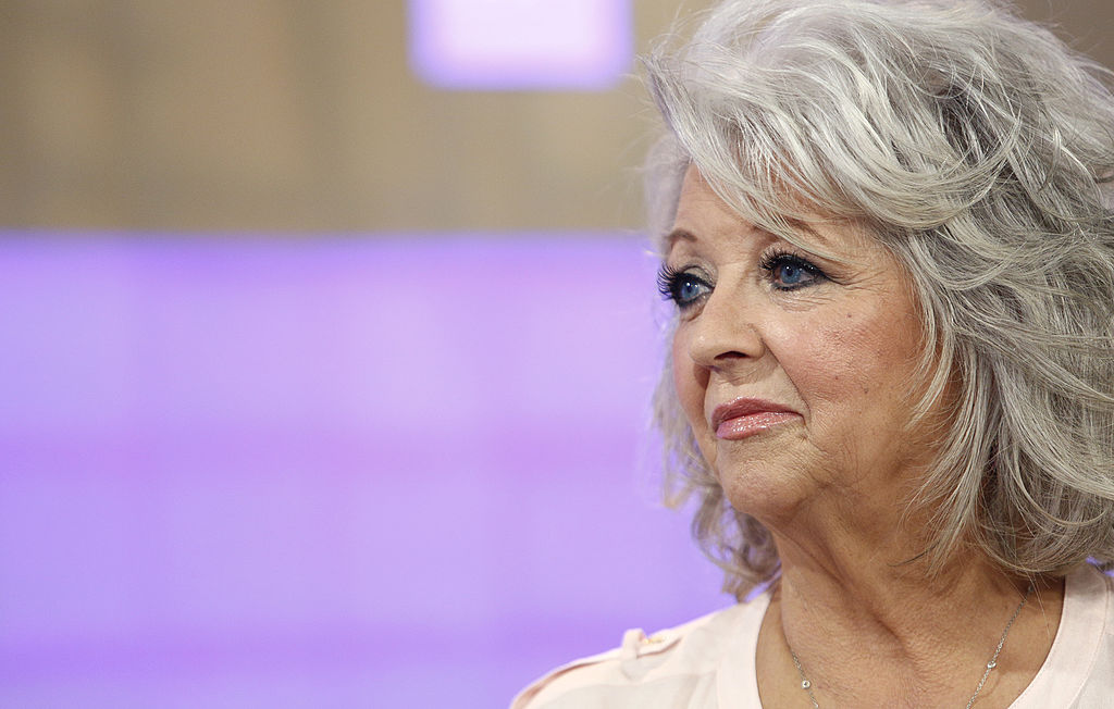 Paula Deen looking off camera in front of a light purple background
