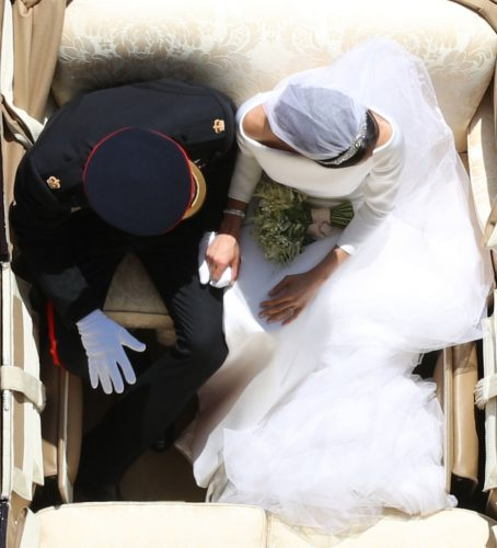 Prince Harry and Meghan Markle hold hands during their carriage procession following 2018 royal wedding