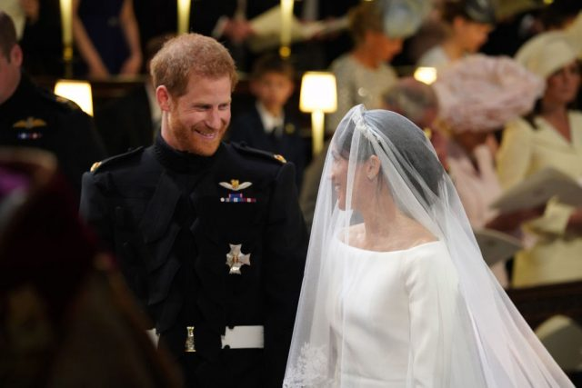 Prince Harry and Meghan Markle smile at each other during their 2018 royal wedding