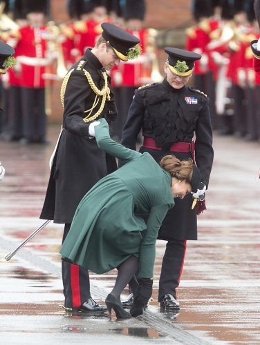 Kate Middleton holds Prince William's hand as she gets her shoe out of a grate
