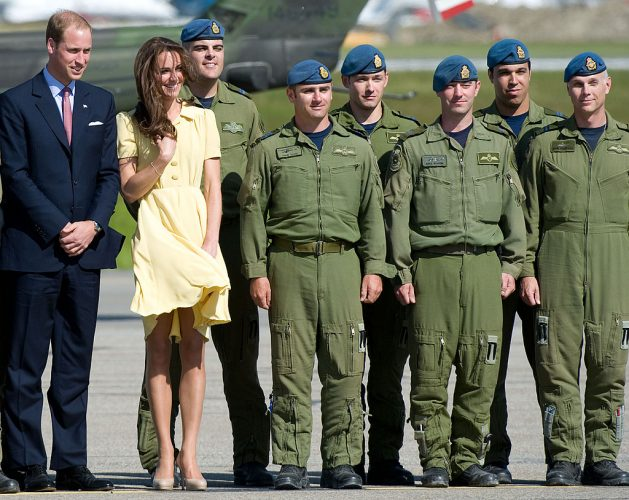 Kate Middleton keeps her hair and dress from blowing in the wind standing next to Prince William and soldiers