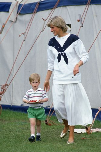 Princess Diana walks with Prince Harry as he holds a plate of strawberries