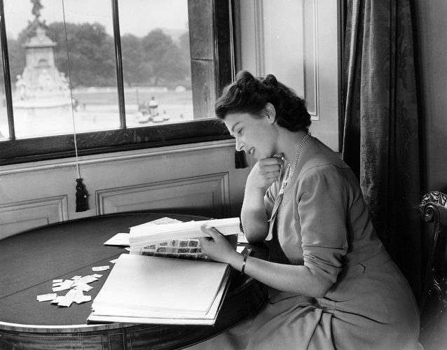 Queen Elizabeth II looking at royal stamp collection