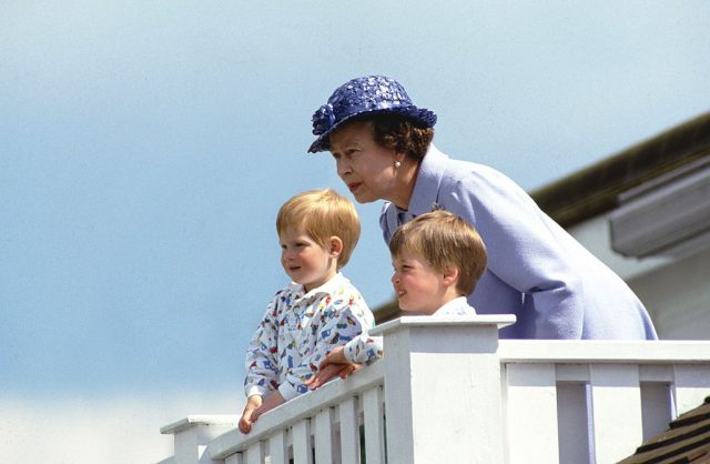 Queen Elizabeth II stands with a young Prince Harry and Prince William at a polo club