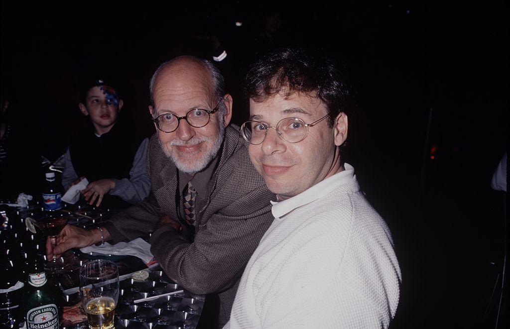 Rick Moranis smiling, looking sideways at the camera