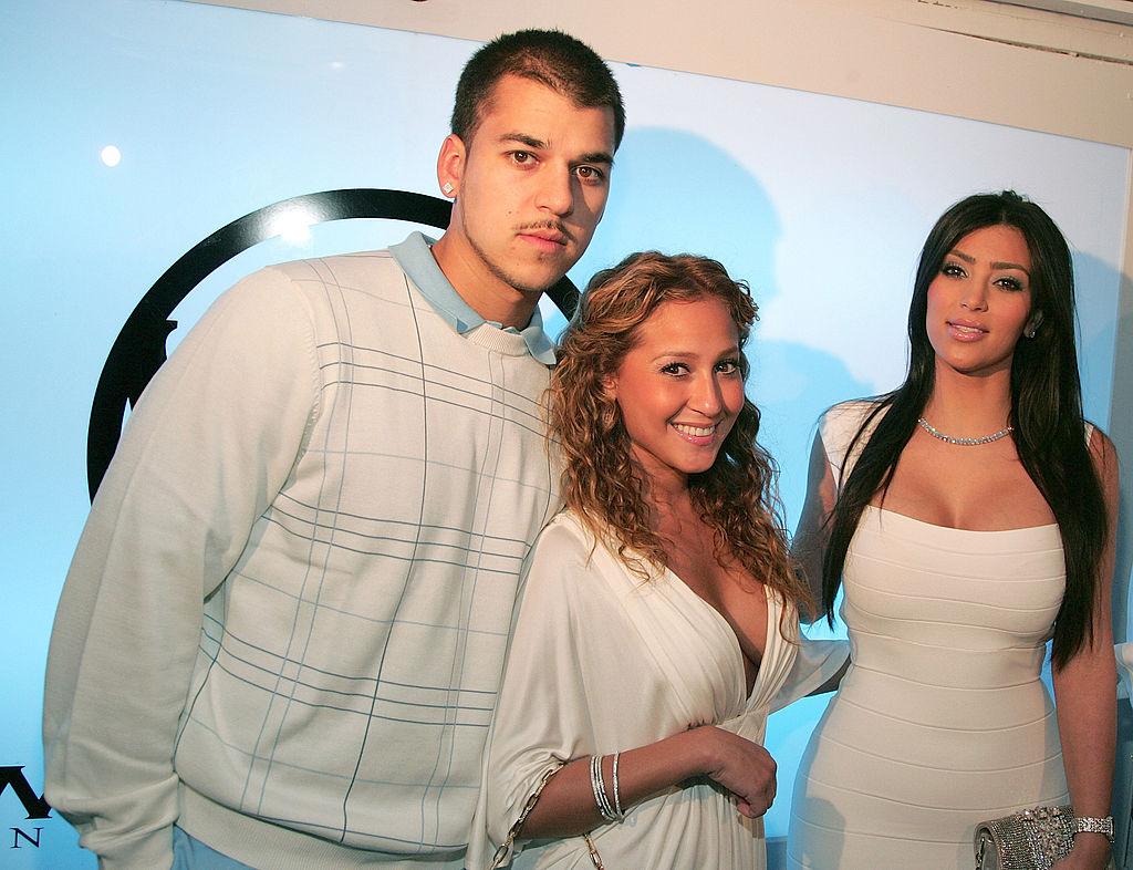 Rob Kardashian Jr. standing with Adrienne Bailon and Kim Kardashian