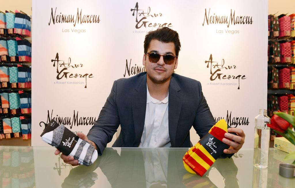 Rob Kardashian wearing sunglasses and a gray blazer holding up two pairs of socks
