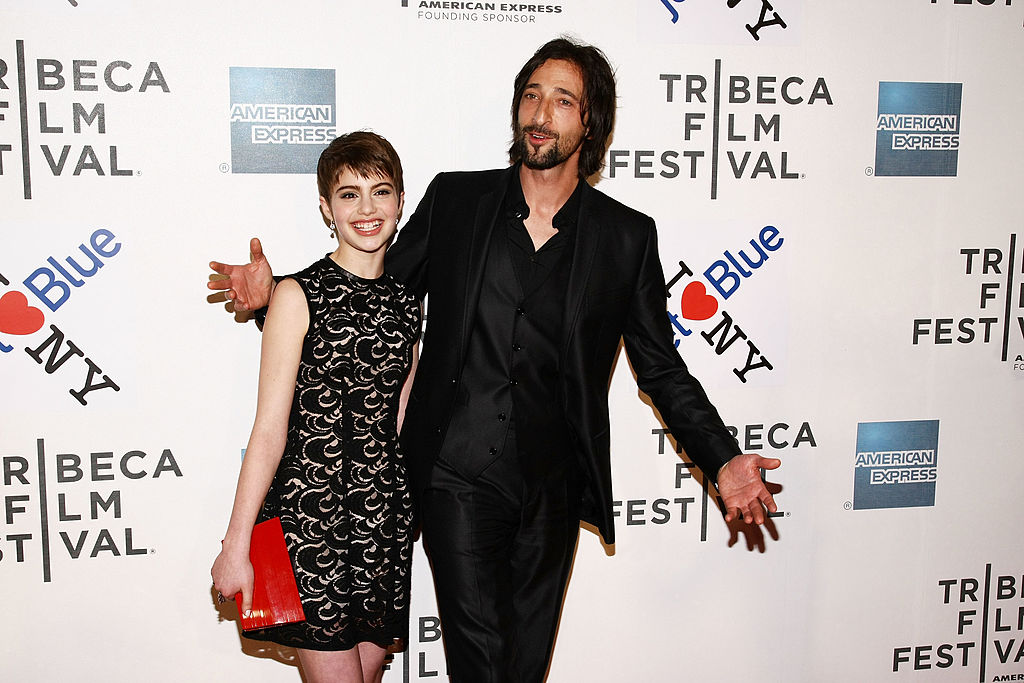 Sami Gayle and Adrien Brody smiling in front of a repeating background