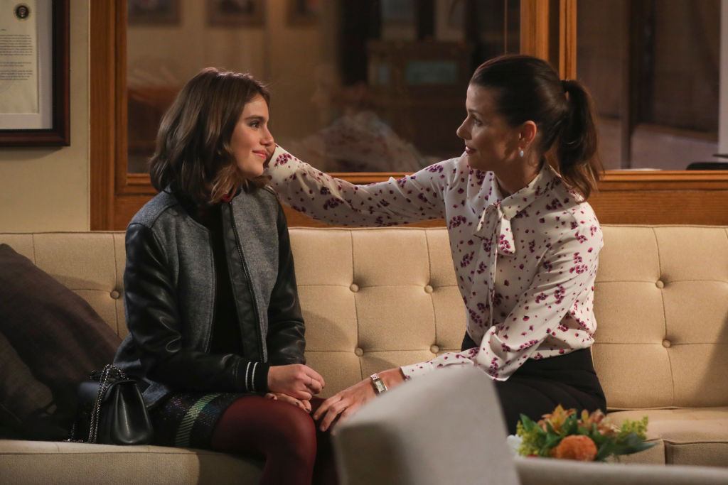 Sami Gayle and Bridget Moynahan sitting on a couch smiling at each other