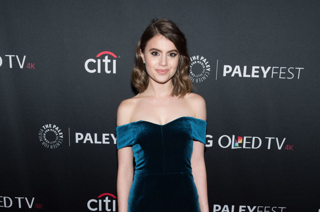Sami Gayle smiling in front of a repeating background in a dark teal velvet dress