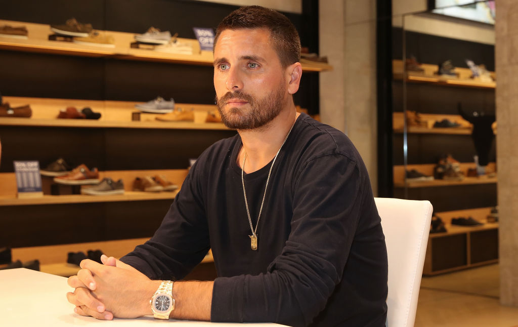 Scott Disick sitting with his hands folded, looking away from the camera