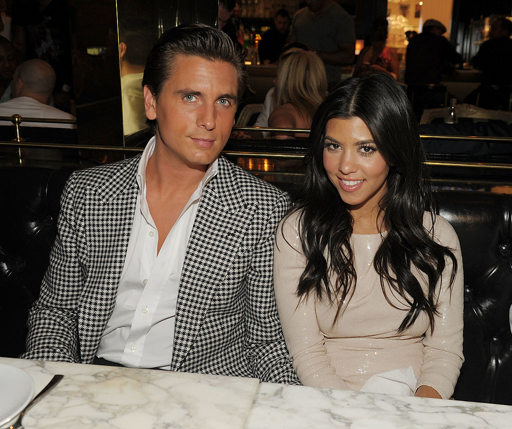 Scott Disick and Kourtney Kardashian smiling at the camera sitting at a table