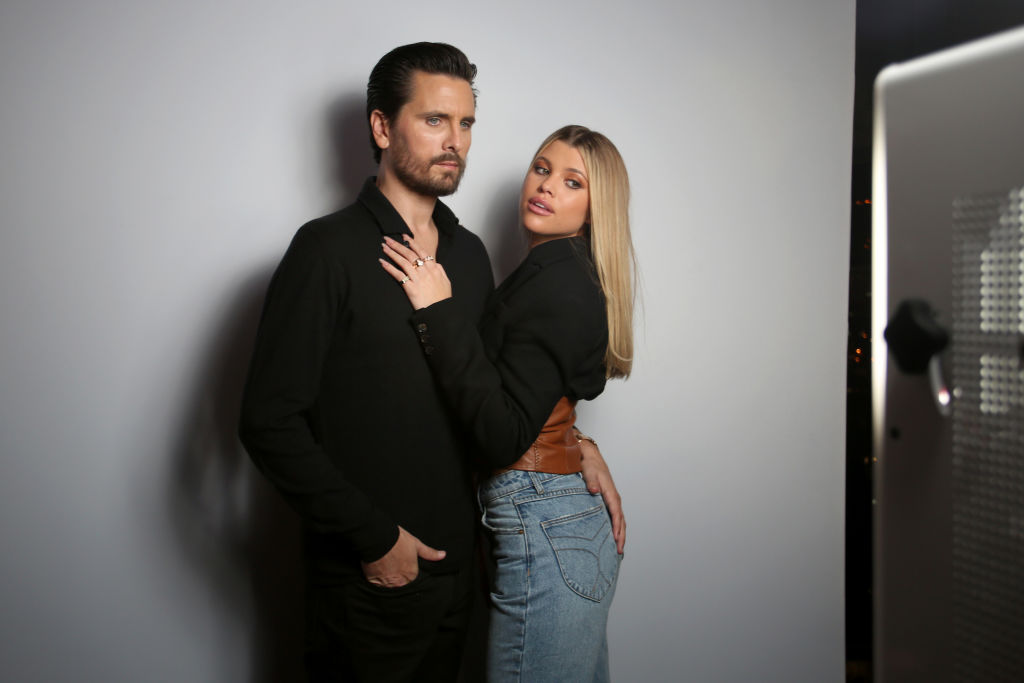Scott Disick with his arm around Sofia Richie, who is looking back at the camera