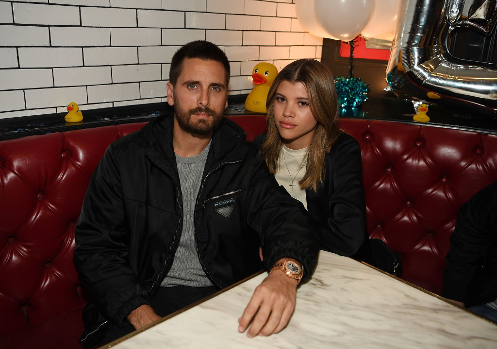 Scott Disick and Sofia Richie smiling sitting at a table