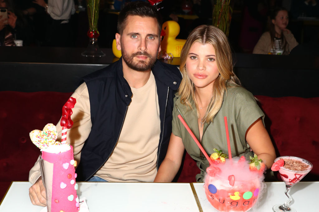 Scott Disick and Sofia Richie smiling at a restaurant table