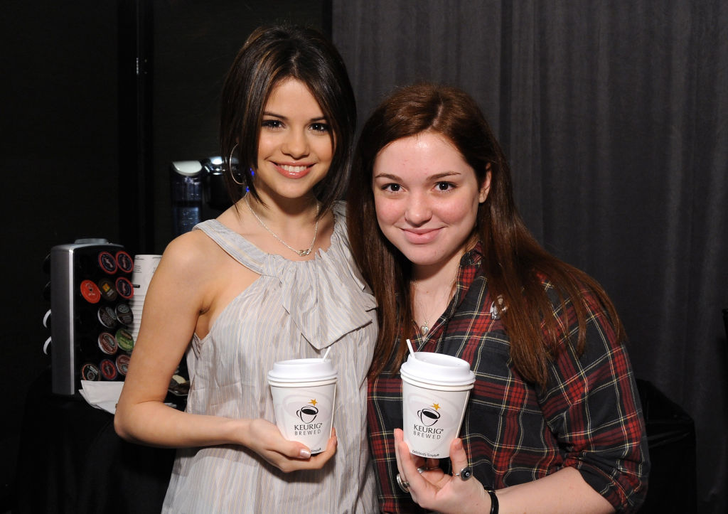 Selena Gomez and Jennifer Stone smiling holding coffee cups