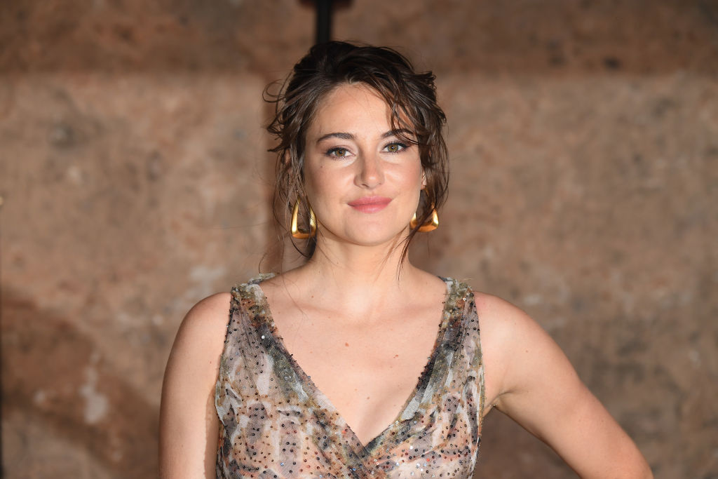 Shailene Woodley smiling at the camera in a beige and white dress