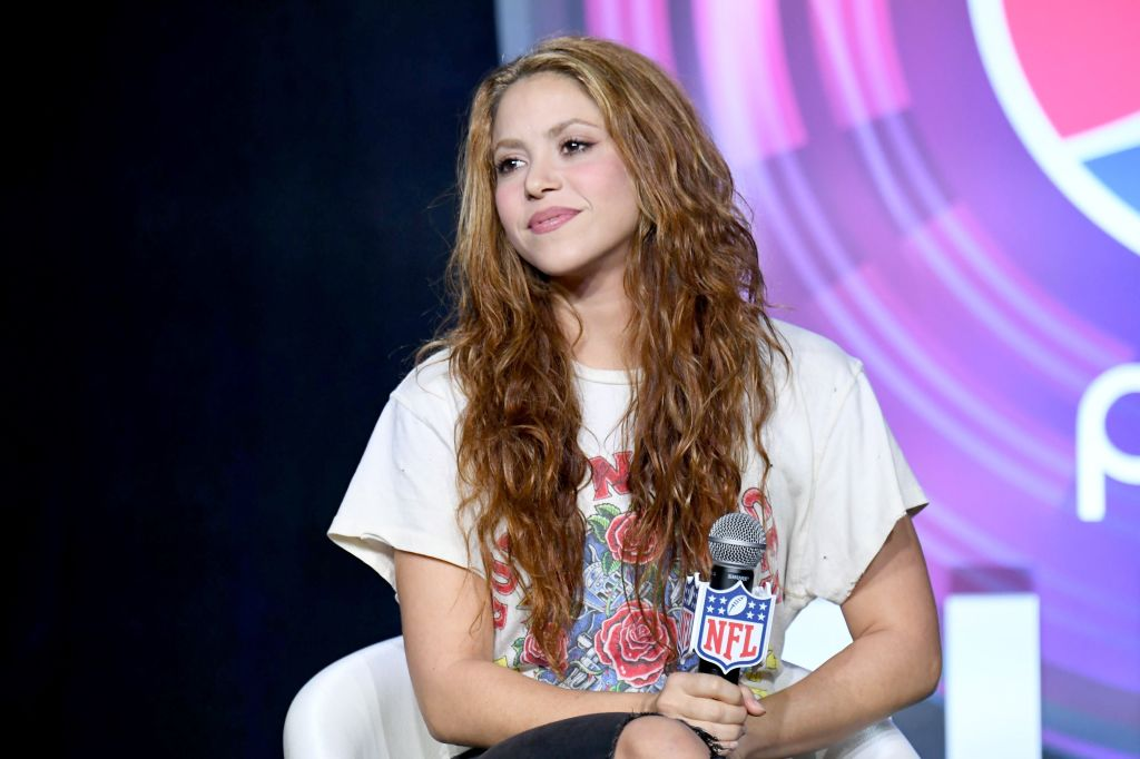 Shakira smiling holding a microphone with an NFL logo