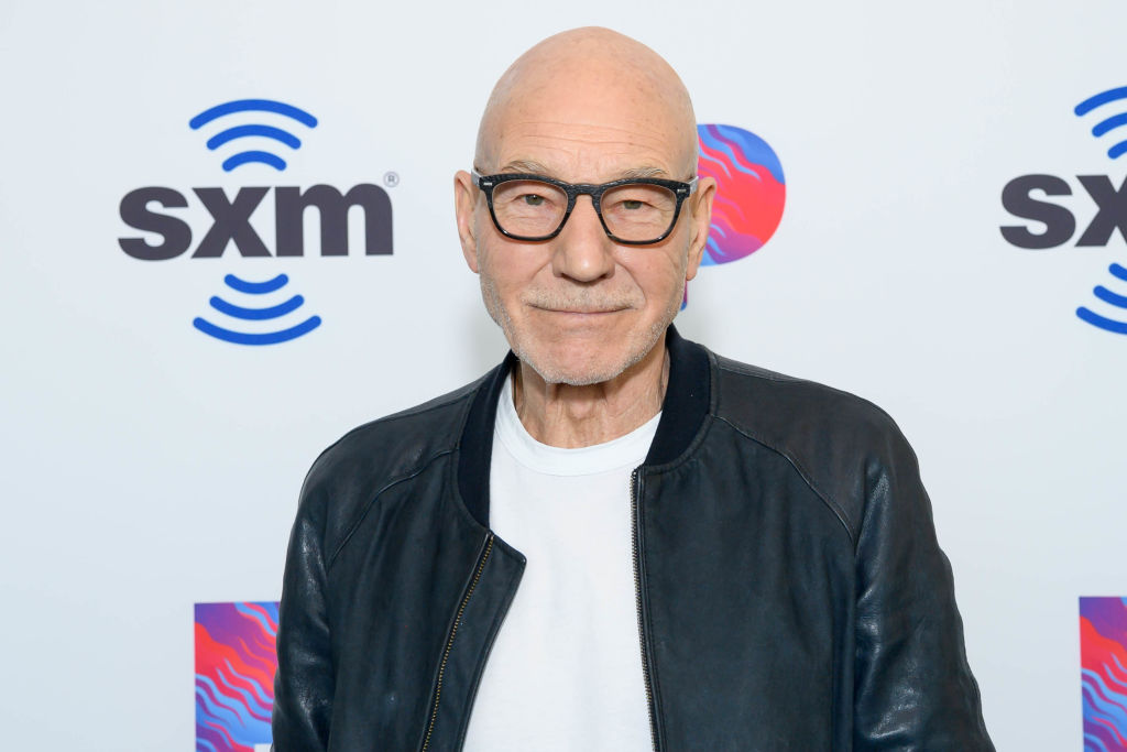Sir Patrick Stewart smiling in front of a white background