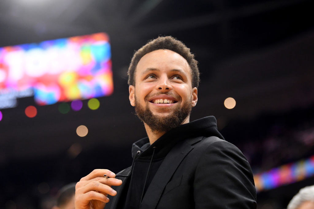 Steph Curry smiling, looking over the camera