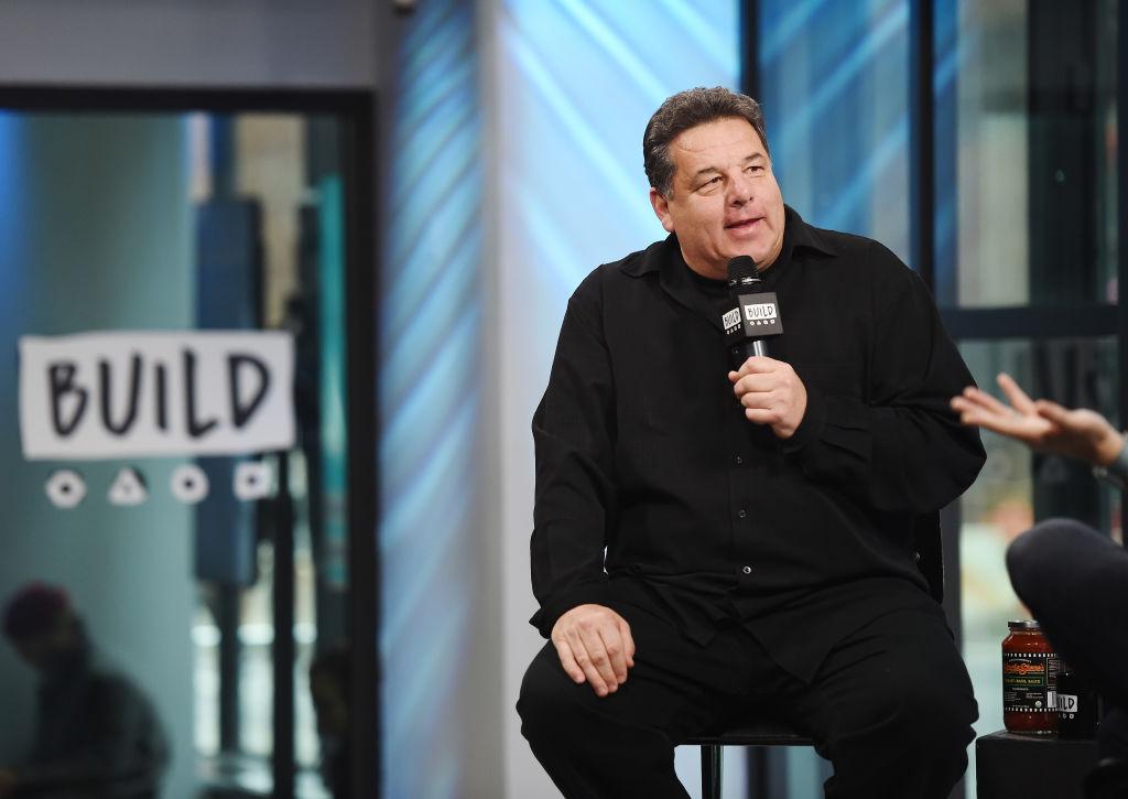 Steve Schirripa smiling, seated, holding a microphone
